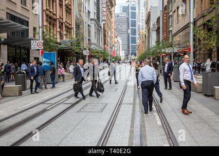 Office workers walk across completed light rail track in Sydney city centre,Australia - Stock Image