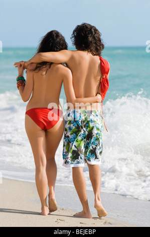 Rear view of a young couple walking on the beach - Stock Image