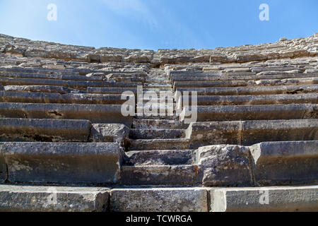 Stone steps of an old amphitheater from ancient times in the region of Antalya, Side, Turkey. - Stock Image