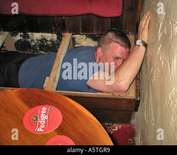 Young man indoor caving in an Inn after a few beers during a stag party weekend - Stock Image