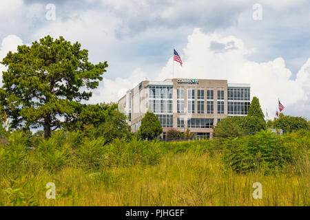 HICKORY, NC, USA-9/6/18: The Commscope corporate building, based in Hickory, stands beyond a green field with bushes and small trees. - Stock Image