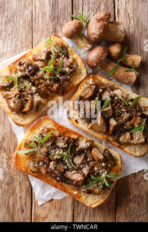 Italian homemade sandwiches with fried boletus mushrooms, onions, thyme and parmesan cheese closeup on the table. Vertical top view from above - Stock Image
