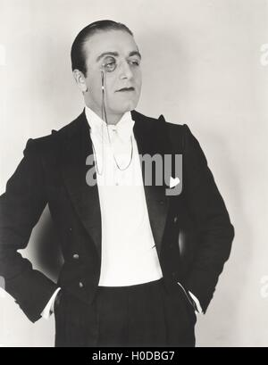 Man wearing monocle and tuxedo with hands in pockets - Stock Image