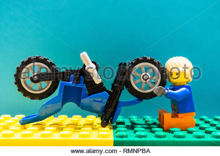 Poznan, Poland - February 13, 2019: Lego toy man character trying to fox a wheel on a motorbike. The vehicle needed some maintenance. - Stock Image