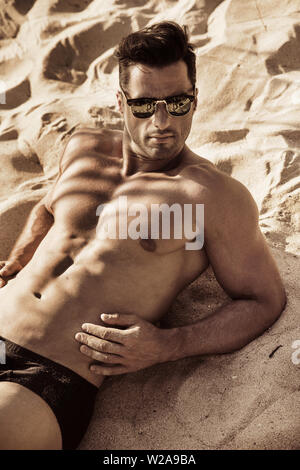 Portrait of a handsome, muscular guy relaxing on a tropical beach - Stock Image