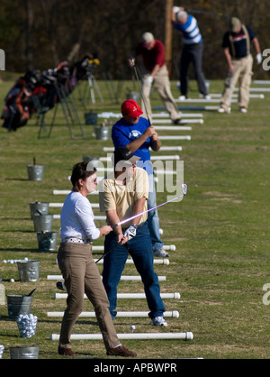 Golfers practice their strokes on the driving range at Tanyard Creek in Bella Vista, Ark. - Stock Image