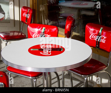 Red coca cola chairs around a white coca cola table - Stock Image