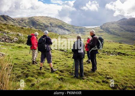 Hikers ramblers in Cwmystradllyn valley looking towards abandoned slate quarry in Snowdonia National Park. Porthmadog, Gwynedd, Wales, UK, Britain - Stock Image