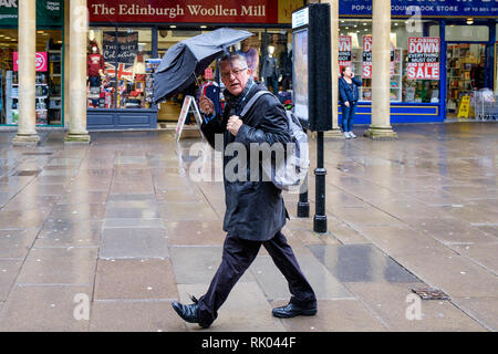 Bath, UK. 8th February, 2019. As storm Eric brings gales and heavy rain across the UK a pedestrian shopping in the centre of Bath is pictured carrying an umbrella as he braves the heavy rain and wind. Credit: Lynchpics/Alamy Live News - Stock Image