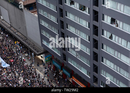 People look out from their apartment windows the mass rally. Nearly two million people joined the demonstration in another round of protest demanding the Hong Kong government to withdraw the extradition bill.Despite the Chief Executive Carrie Lam's attempt to ease the heightened tension by agreeing to suspend the controversial bill, close to 2 million people participated in Sunday's rally, according to the organizers. The protesters called for the withdrawal of the controversial extradition bill, the release and non-prosecution of the people arrested due to the cause, investigation of whether - Stock Image