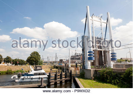 Vlaardingen The Netherlands Pleasure motorboat passing under a railway drawbridge. - Stock Image