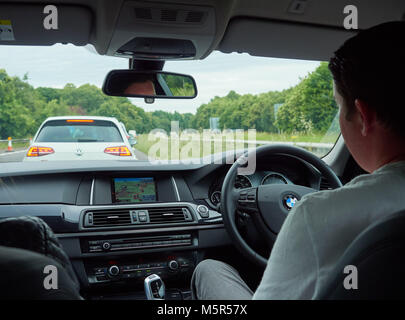 A car interior and driver of a car stuck in traffic from roadworks on a motorway. - Stock Image