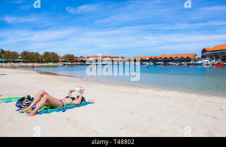 A teenage girl sunbathing and reading a book on the beach at Sorrento Quay Hillarys Boat Harbour. - Stock Image