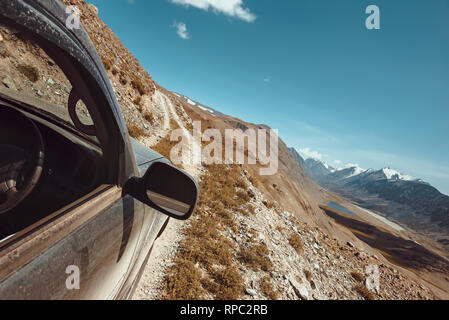 Offroad concept with 4x4 car on dangerous road and mountains on background - Stock Image