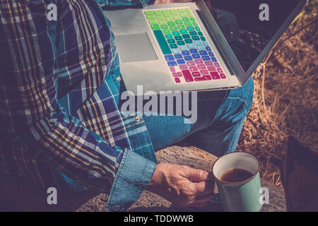 Travel and technology concept for modern mature senior people - hipster retired woman sit down with coloured computer laptop in the nature with a cup  - Stock Image