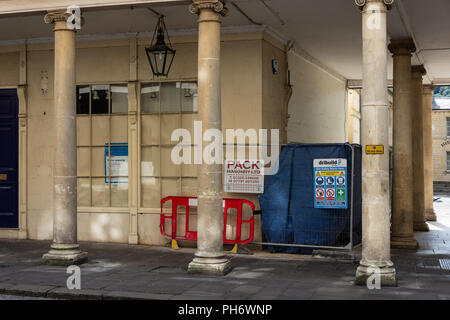 A bath building including ionic column with safety barriers and notices of building work being done - Stock Image