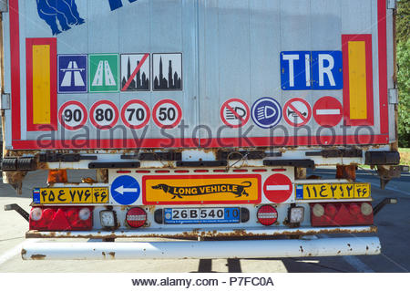 Rear of an Iranian registered truck, showing an assortment of highway code information signs, and a long vehicle (with dachshund dog) reflector plate. - Stock Image