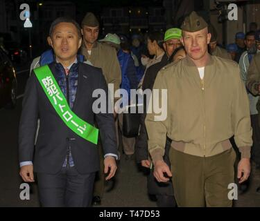 Yoshihiko Fukuda, left, the mayor of Iwakuni City, and U.S. Marine Corps Col. Richard Fuerst, commanding officer of Marine Corps Air Station Iwakuni, participate in the 10th Joint Leadership Walk in Iwakuni City, March 15, 2019. The walk consisted of touring popular local areas where they spoke to business owners as well as Japanese and American customers. - Stock Image