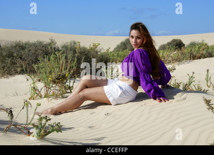Indonesian Girl in a Purple and White Outfit Sitting on Sand Dunes, Fuerteventura, Canary Islands, Spain. - Stock Image