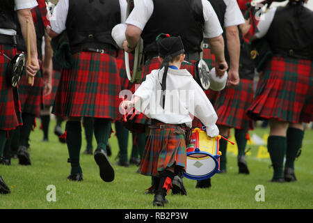 Little Boy plays the drum at Highland games - Stock Image