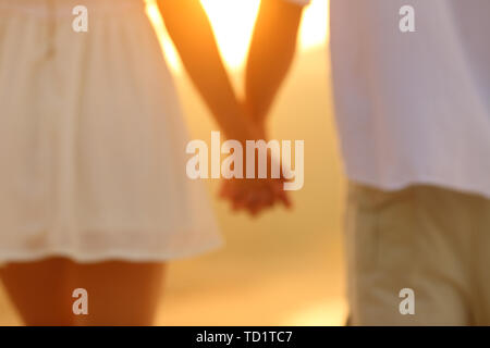 Back view portrait of a blurred couple holding hands at sunset - Stock Image