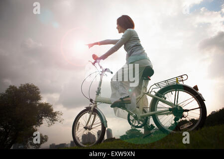 Young woman riding a bike and pointing away, - Stock Image