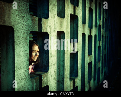 Girl looks through patterned concrete block wall - Stock Image