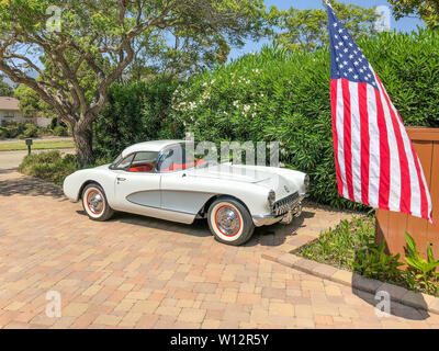 Side view of a  white with silver 1957 Corvette with the optional hardtop with the American flag in front of the car. - Stock Image