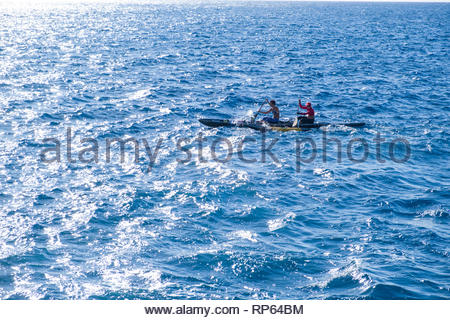 Two people paddling an outrigger racing canoe at Pai'olu'olu point, Koko Head, Koko Head District Park, Hawaii Kai, Oahu, Hawaii, USA - Stock Image