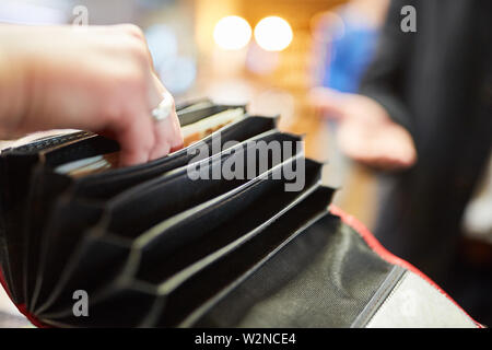 Man looking in the wallet for a bill while paying with cash - Stock Image