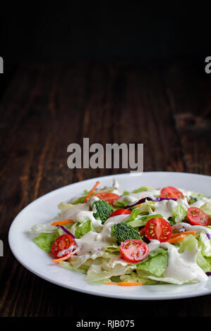 Plate of homemade fresh salad with buttermilk ranch dressing, tomatoes, broccoli, cabbage and carrots over a rustic wooden table and dark background.  - Stock Image