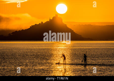 Penzance, Cornwall, UK. 28th Mar, 2019. UK Weather. Paddleboarders were out at 5am this morning to make it across the sea at Mounts bay the for the sunrise over St Michaels Mount. Credit: Simon Maycock/Alamy Live News - Stock Image