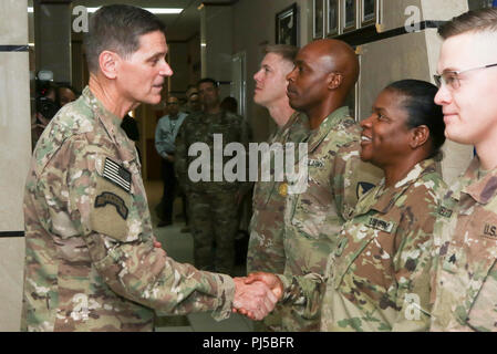 U.S. Army Gen. Joseph Votel, U.S. Central Command commander, presents a coin to U.S. Army Sgt Barbara Y. Swaso, a staff accountant assigned to Area Support Group-Qatar, during his visit to Camp As Sayliyah, Qatar, August 30, 2018. The visit provides Gen. Votel with a deeper understanding of the unique capabilities ASG-Qatar and U.S. Army Central Soldiers provide to USCENTCOM's mission and the opportunity to recognize persistent excellence in our military. (Photo by U.S. Army Sgt. James Lefty Larimer) - Stock Image