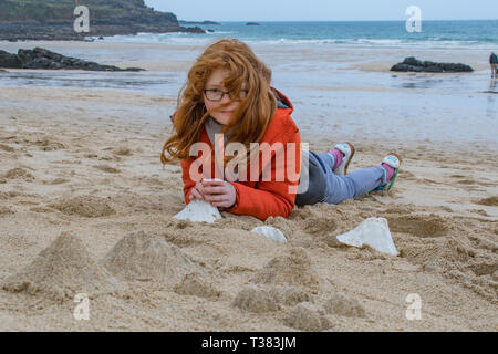 St Ives, Cornwall, UK. 7th April 2019.  The public were invited to cover the beach at St Ives with tiny mountains, made from moulds to represent Mount Kilmanjaro,  Shasta, Fuji, Stromboli and Ulura. Seen here Agatha Fitch.  The event today organised by the Tate St Ives is one of several taking place around the UK in conjunction with artist Katie Paterson. Credit: Simon Maycock/Alamy Live News - Stock Image