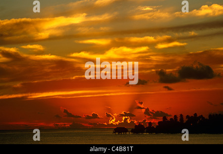 French Polynesia, Society Islands, Leeward Islands. A brilliant sunset frames a Polynesian idyll of over-water bungalows - Stock Image