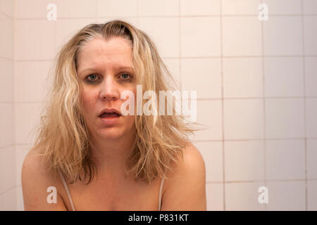 A woman with horrible messy hair, dark black circles under eyes and rough looking face feels sick, hungover or ill - Stock Image