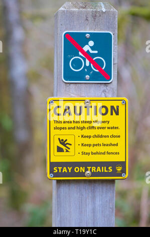 Yellow Caution Sign and a No biking sign warning people to stay on the trails as the area has slippery slopes and high cliffs over water. - Stock Image