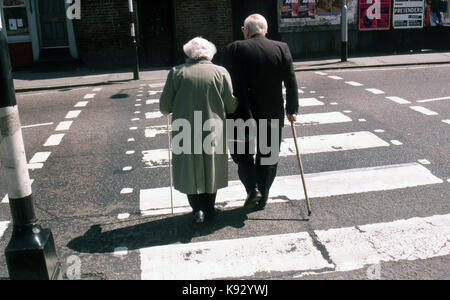 Back view of an elderly couple walking on a pedestrian crossing with man aided by a walking stick and the woman - Stock Image