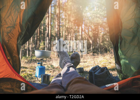 wanderlust outdoor camping - traveler feet out of the tent - Stock Image