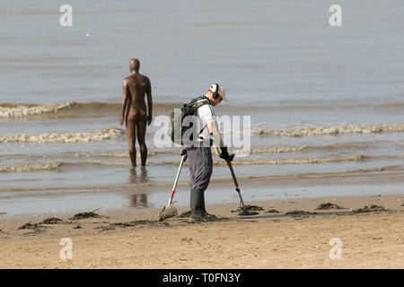 Crosby, Merseyside. 20th March, 2019. Most successful after a storm, local beachcombers scour the shoreline for disturbed treasure on a warm hazy spring day for metal detecting at the coast. Looking for treasure, equipment, discovery, history, sensor, adventure, electrical, searching, detect, finding lost items. holding detection instrument. Credit: MWI/AlamyLiveNews - Stock Image