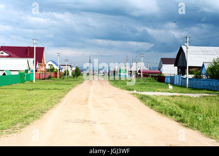 Typical Russian street in a village with dust path leading to overcast summer skies with nobody - Stock Image