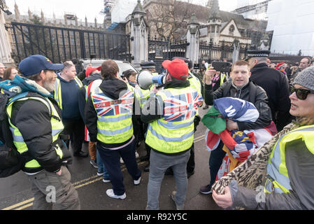 London, UK. 19th December 2018. A small group of extreme right Brexiteers wearing high-viz vests protested outside parliament calling for an immediate Brexit and attempt to stop vehicles leaving parliament and are moved away by police. One carries a rolled up large banner showing them to be Arsenal supporters, and they had spent some hours earlier yelling insults at the regular SODEM pro-EU protesters. Credit: Peter Marshall/Alamy Live News - Stock Image