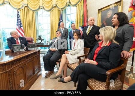 """U.S President Donald Trump, joined by Cabinet members talks with workers during the """"Cutting the Red Tape and Unleashing Economic Freedom"""" event in the Oval Office of the White House October 17, 2018 in Washington, DC. - Stock Image"""