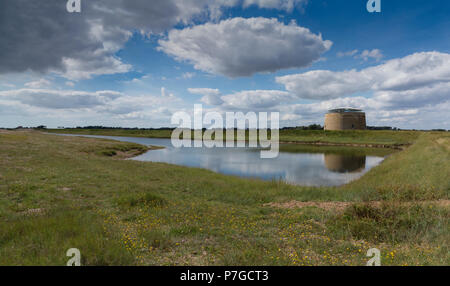 A Martello tower standing behind a small lake and reflected in it with clouds and blue sky, Suffolk, England - Stock Image