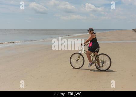 Woman Peddling bicycle on Beach Shoreline - Stock Image