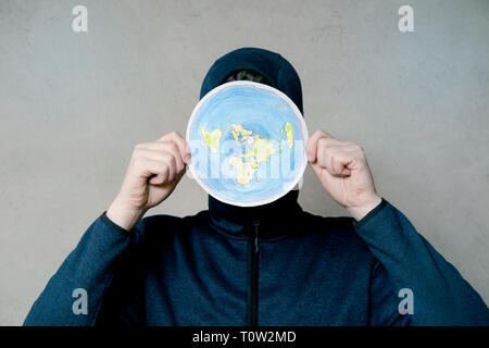 Flat Earther concept. Person who believes that Earth is flat disc. Anonymous hooded Man holding flat Earth model in front of face, copy space. Isolate - Stock Image
