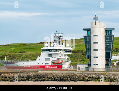 Ostensjo Rederi Norwegain ship Edda Sun leaving Aberdeen harbour with shipping control tower, Scotland, UK - Stock Image