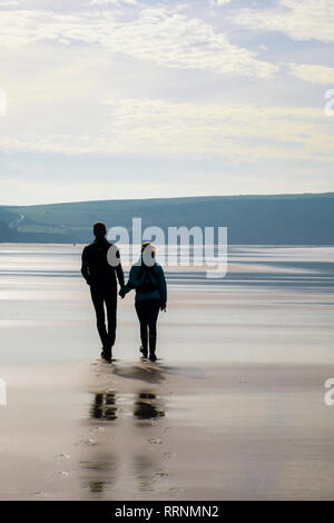 A couple holding hands walking on a quiet sandy beach at low tide. Woolacombe, North Devon, England, UK, Britain - Stock Image