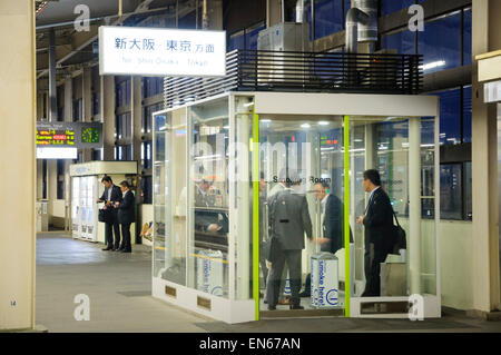 Glass box with ventilation system for smokers, allowing them to smoke on the station platform where smoking is otherwise - Stock Image