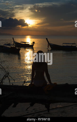 Silhouette of a girl sitting on a fallen tree on the beach, Ko Lipe, Thailand - Stock Image